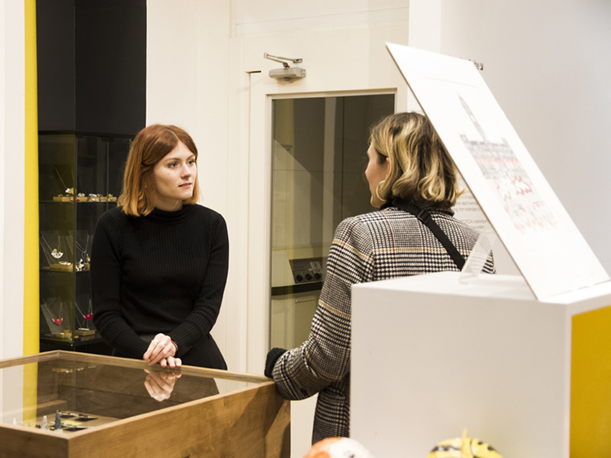 Photograph of member of staff speaking to a customer in CFCCA shop