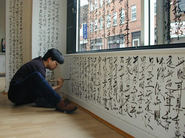 Photograph of Chun-Chao Chiu installing work in 2001